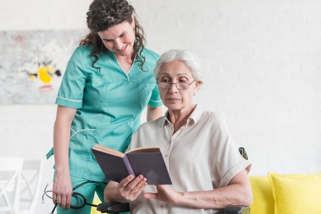 Smiling nurse looking at book hold by female senior patient sitting on wheel chair