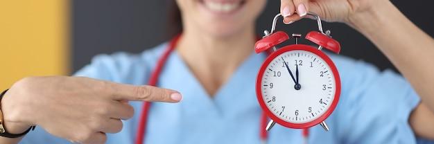 Smiling nurse points finger at red alarm clock