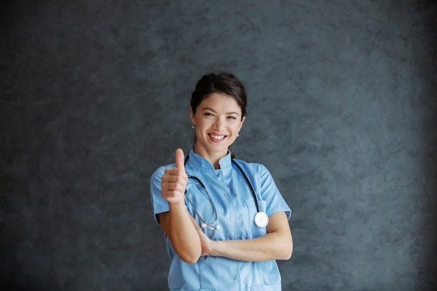 Улыбающаяся медсестра со стетоскопом позирует и показывает палец вверх. здоровье хорошее.