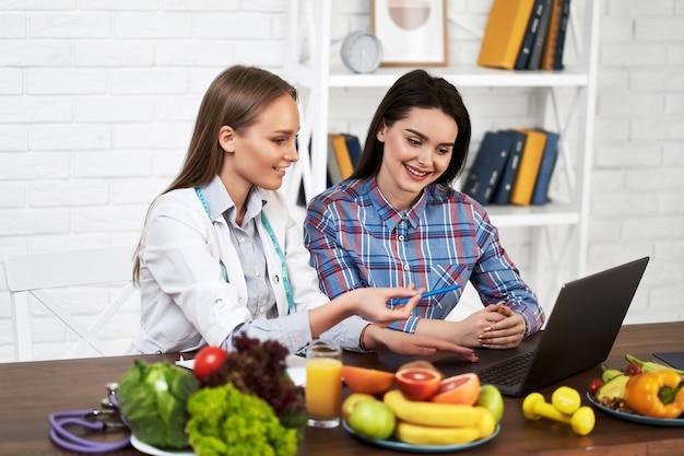 Un nutrizionista sorridente consiglia una giovane donna paziente su una corretta alimentazione e dieta