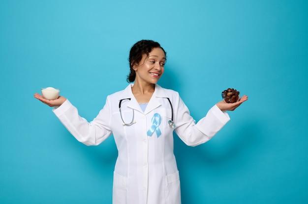 Улыбающийся диетолог в медицинском халате с голубой лентой держит в одной руке миску с рафинированным белым сахаром, а в другой - спелые сладкие финики. концепции сахара и диабета ко всемирному дню осведомленности о диабете