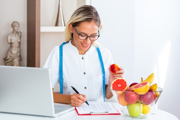 Smiling nutritionist in office holding a fruit