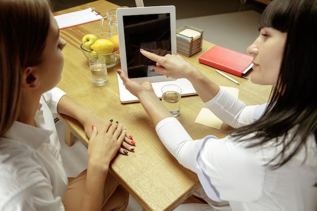 患者に健康的な食事療法の計画を示す笑顔の栄養士。栄養の推奨事項を持っているために医者を訪問している若い女性。健康的なライフスタイルと食品、薬と治療の概念。