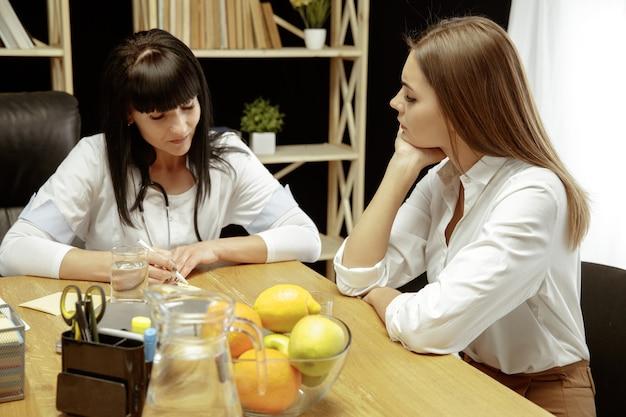 医師を訪問している患者の若い女性に健康的な食事療法の計画を示す笑顔の栄養士
