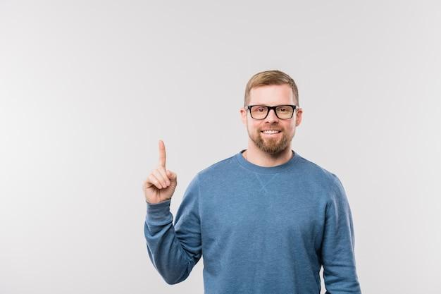 Улыбающийся офис-менеджер в повседневной одежде, указывая вверх, стоя перед камерой и глядя на вас