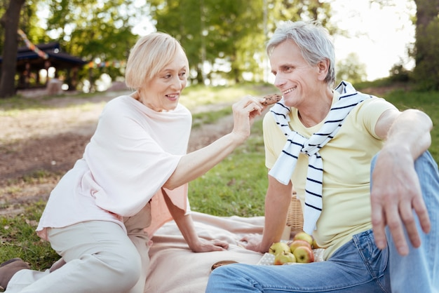 Smiling old loving couple expressing happiness while enjoying picnic outdoors and eating dessert