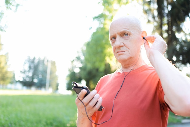 Smiling old man in casual wear and white headphones listening music from his smartphone in city park at sunny day.
