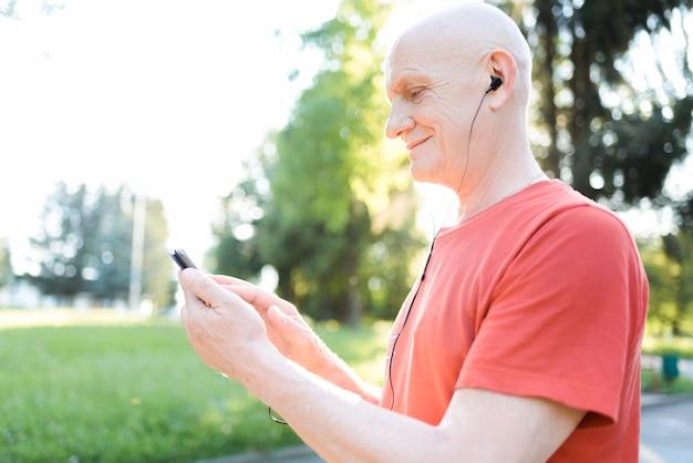 화창한 날에 도시 공원에서 자신의 스마트 폰에서 음악을 듣고 캐주얼과 흰색 헤드폰에 노인을 웃 고.