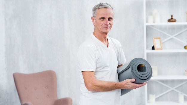 Smiling old man standing at home with rolled yoga mat