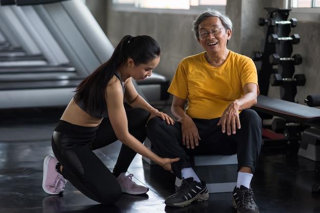 健康な女性による応急処置マッサージの後、右脚の痛みと脚の痛みからの解放を伴う笑顔の老人。体育館で老齢年金受給者に負傷した脚をマッサージ。スポーツ事故のコンセプト。