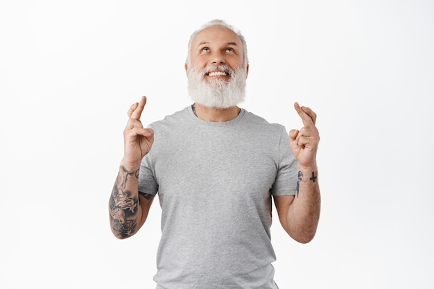 Smiling old man with tattoos looking up in sky, make wish and cross fingers for good luck, praying, begging god for fortune or dream come true, standing against white wall
