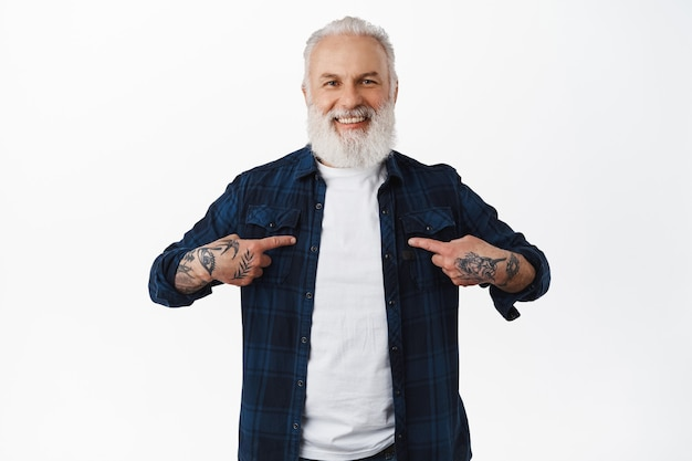 Smiling old stylish guy with tattoos and beard, pointing at himself, choose me, wants to volunteer, nominating him, boasting or self-promoting, standing over white wall