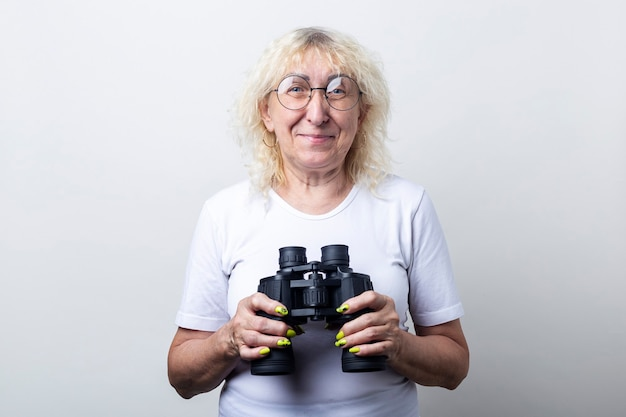 Smiling old woman in glasses with binoculars on a light background.