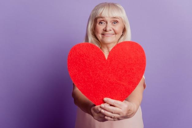 Улыбающаяся старуха держит большую валентинку в форме сердца, изолированную на фиолетовом фоне