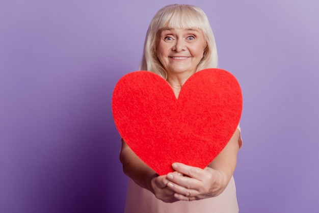 Smiling old woman hold big valentine heart card isolated on violet background