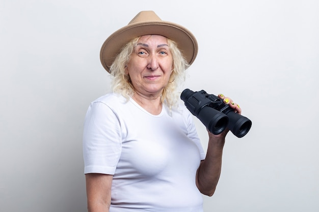 Smiling old woman holding binoculars on a light background.