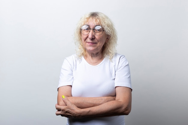 밝은 배경에 안경을 쓴 흰색 티셔츠를 입은 웃는 노파.