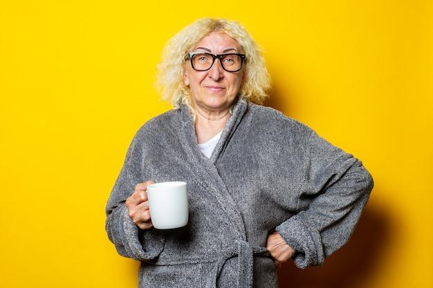 Улыбающаяся старуха в очках и сером халате с чашкой