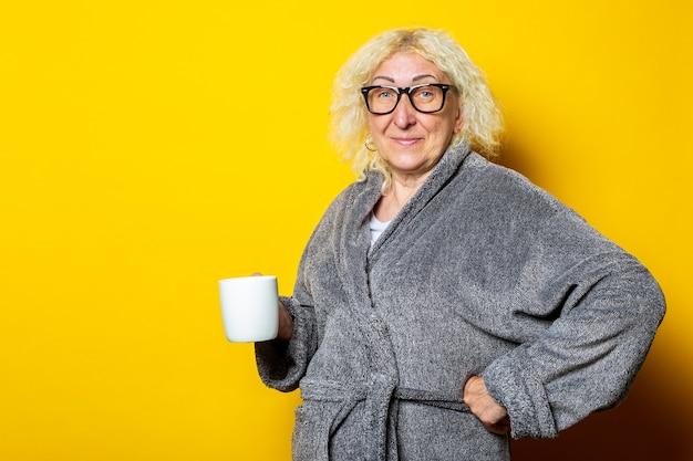 Улыбающаяся старуха в сером халате держит чашку с кофе