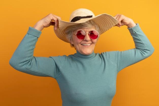 Sorridente anziana che indossa un maglione blu a collo alto con cappello da spiaggia e occhiali da sole che afferra il cappello isolato sul muro arancione