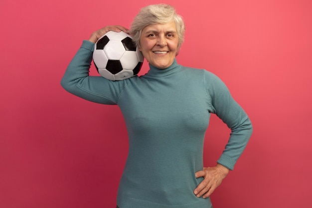 Smiling old woman wearing blue turtleneck sweater holding soccer ball on shoulder keeping hand on waist isolated on pink wall