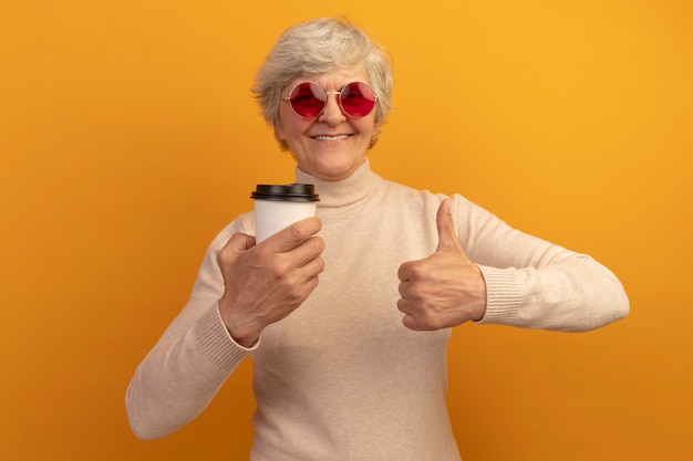 クリーミーなタートルネックのセーターとサングラスを身に着けている老婆の笑顔は、オレンジ色の壁に分離された親指を示すプラスチックカップのコーヒーを保持しています
