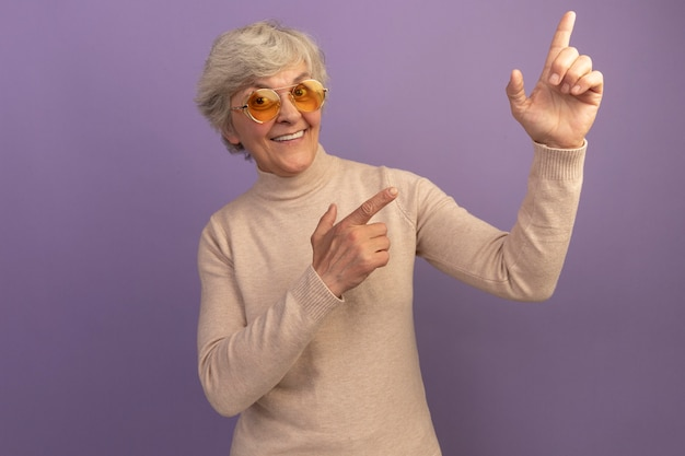 Smiling old woman wearing creamy turtleneck sweater and sunglasses pointing up