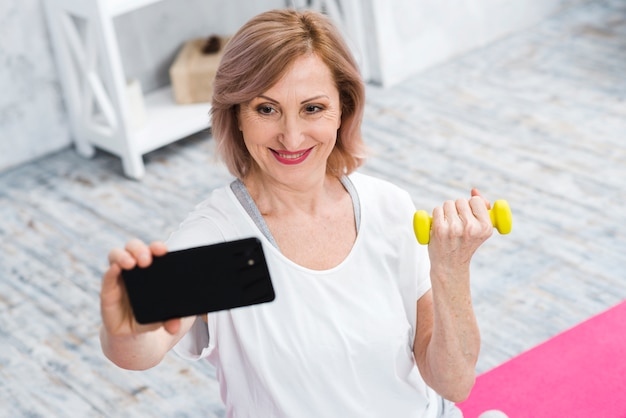 Smiling old woman with dumbbells taking selfie using cell phone