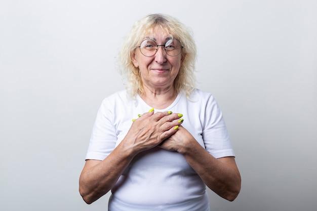 안경을 쓴 웃는 노파는 밝은 배경에서 가슴에 손을 얹고 있습니다.