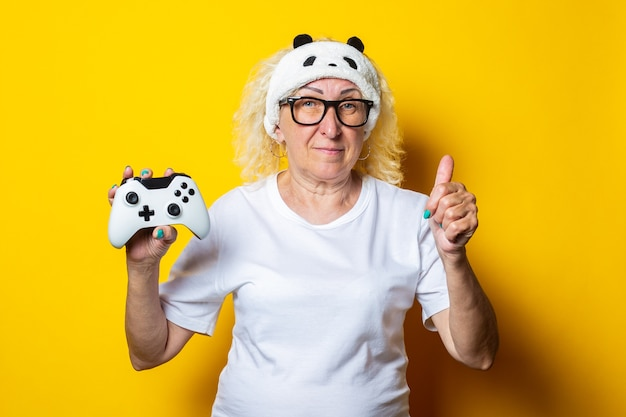 Smiling old woman with joystick in sleep mask shows thumb up hand gesture
