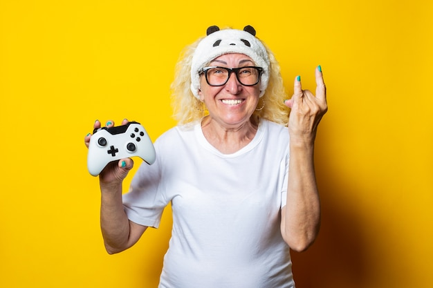 Smiling old woman with a joystick in a sleep mask shows