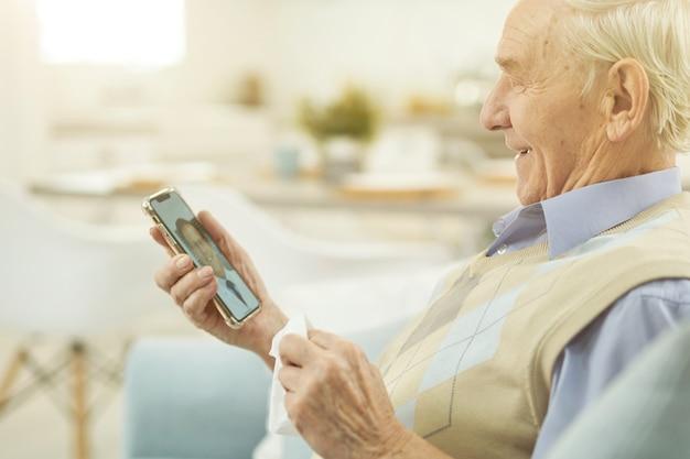 스마트폰을 보고 의사와 온라인 채팅을 하는 웃고 있는 노인