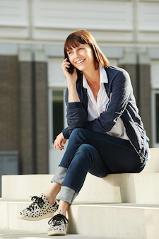 Smiling older woman sitting on stairs with smart phone