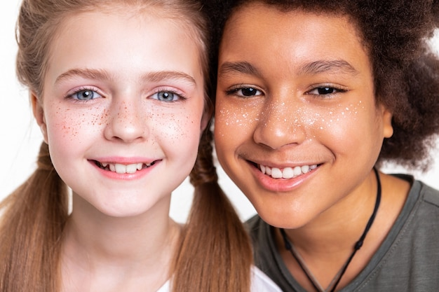 カメラに微笑んでいます。写真を撮り、広い笑顔を見せながら顔をつなぐ平和で魅力的な子供たち