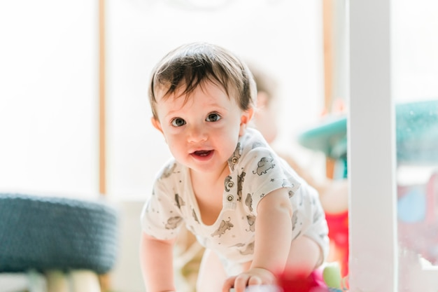 Smiling one year old boy crawling at home
