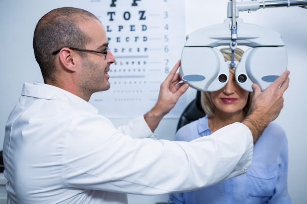 Smiling optometrist examining female patient on phoropter