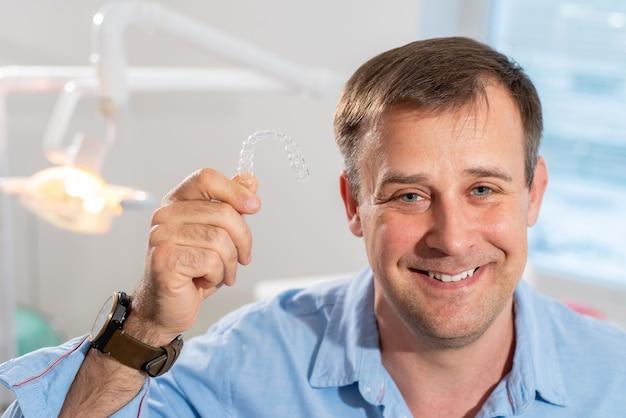 웃는 치열 교정 의사가 그의 손에 투명 정렬기를 보유하고 있습니다.