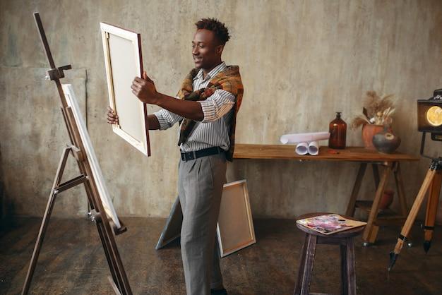 イーゼルの近くに立っているキャンバスと笑顔の画家。男性アーティストが職場で描き、クリエイティブなマスターがワークショップで作品を制作