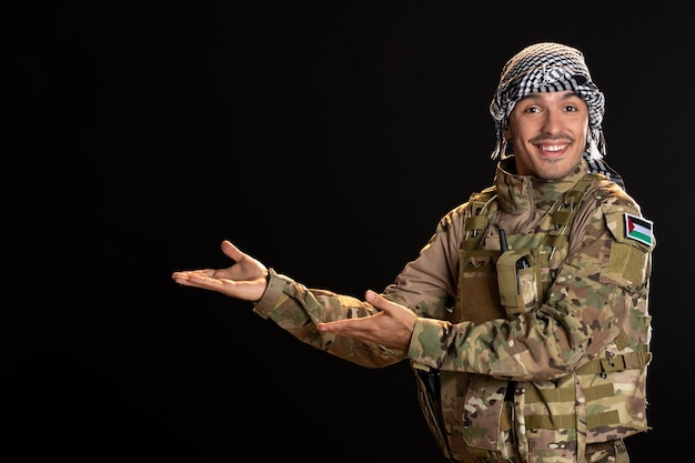 Smiling palestinian serviceman in military uniform on black wall