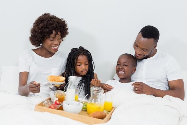 笑顔の両親と子供の寝室で朝食をとり