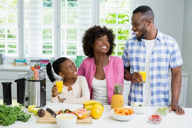Smiling parents and daughter having a glass of orange juice in kitchen at home