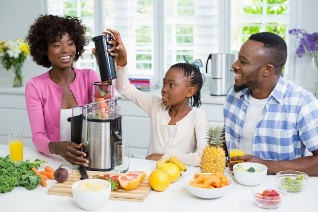 Smiling parents and daughter preparing strawberry smoothie in kitchen