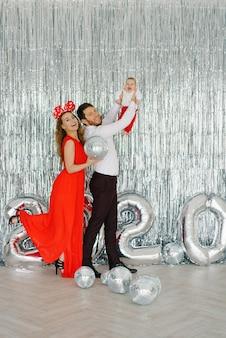 Улыбающиеся родители держат ребенка на руках и провожают старый год, встречают новый год
