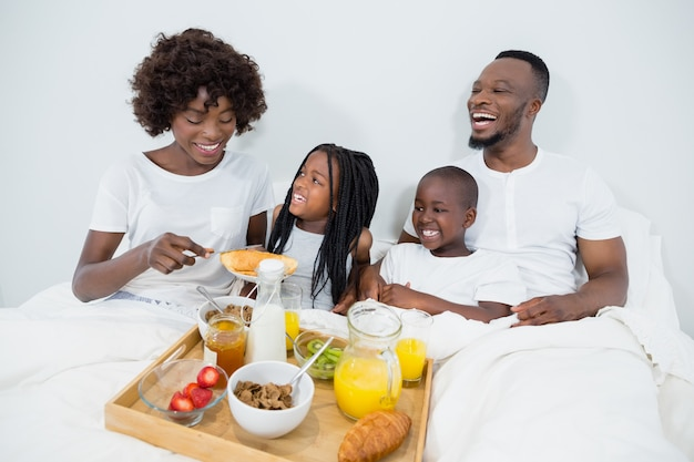 Smiling parents and kids having breakfast in bedroom
