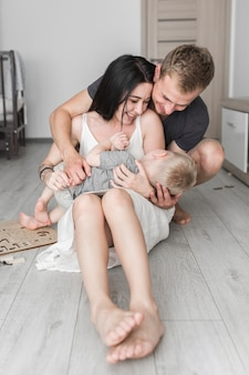 Smiling parents sitting on hardwood floor loving their cute son