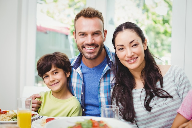 Smiling parents and son at dining table