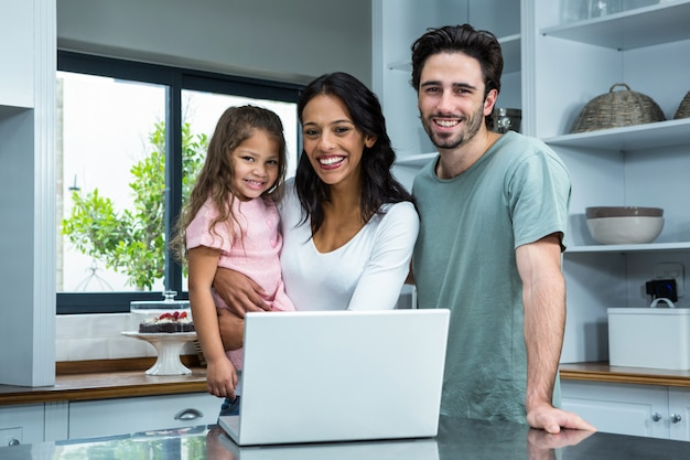 Smiling parents using laptop with daughter