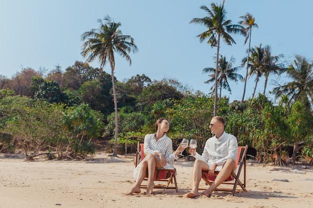 Улыбающиеся партнеры наслаждаются напитками шампанского, отдыхая на удобных стульях у морского пляжа