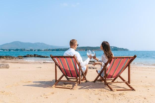 Улыбающиеся партнеры наслаждаются напитками шампанского, отдыхая на удобных стульях у моря