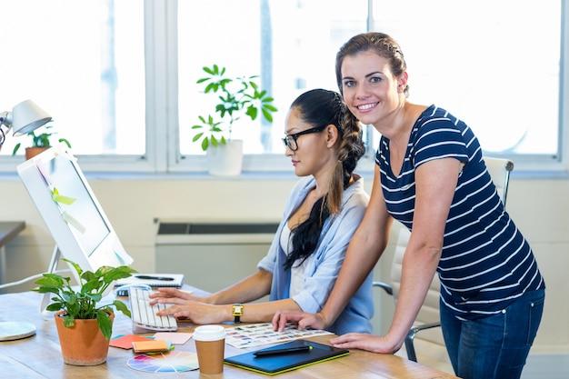 コンピュータで一緒に働く笑顔のパートナー